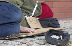 Beggar falling asleep on the street